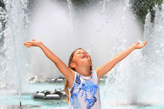 Girl screaming with delight by fountain. Pretty little girl holding her arms in the air with delight next to a fountain royalty free stock images