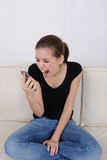 Girl screaming at her cellphone. Angry girl screaming at her cellphone royalty free stock image