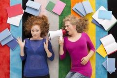 Girl screaming at her friend with loudspeaker. Shot of a young student girl screaming at her friend with loudspeaker Stock Photo