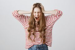 Girl screaming from mental instability. Portrait of depressed fed up young woman shouting and holding hands on head. Closing eyes, being stressed and miserable Stock Image