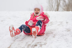A girl screaming and shrieking ice slides down hill Royalty Free Stock Photo