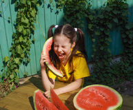 Girl screaming in the watermelon like in the phone Royalty Free Stock Photos