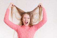 Girl screams hair raising his hands above him. Portrait of a young emotional beautiful girl of the European appearance on a white background Royalty Free Stock Image