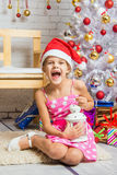 Girl screams happily holding candle in her hands and sitting by Christmas trees Royalty Free Stock Photography