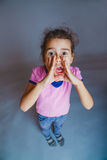Girl screams leaning hand over his mouth isolated Royalty Free Stock Images