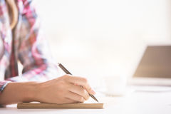 Girl& x27; scrittura della mano di s in blocco note Fotografia Stock