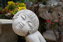 Girl sculpture in the garden. Royalty Free Stock Images