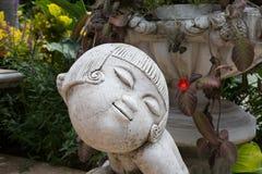 Girl sculpture in the garden. Stock Photos