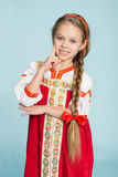Girl with a scythe in Russian folk costume. Blond girl with a scythe in the traditional Russian folk costume. Girl seven years stock image