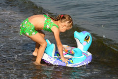 The girl on the sea. The girl plays with a toy on seacoast Royalty Free Stock Photo