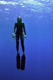 Girl and sea. Young girl with long fins rise from the deep of sea to the surface and sun Royalty Free Stock Images
