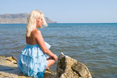 Girl and the Sea. The girl sitting on a rock against the sea and blue sky Stock Photography