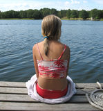 Girl by the sea. Sitting on a towel and watching for boats Royalty Free Stock Photos