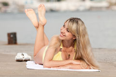 Girl at the sea. Attractive young woman in yellow swimsuit lying on the pier Royalty Free Stock Photos