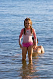 Girl in the sea. Girl walking in the sea after playing the sand Royalty Free Stock Photo