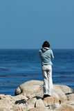 Girl by the Sea. A young woman stands alone looking out into the Pacific ocean Royalty Free Stock Image