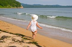 Girl and the sea. The little girl runs on a beach.Summer Royalty Free Stock Photo