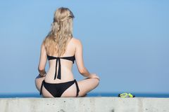 Girl in black bikini with hands on knees at sea. Girl at the sea. Attractive young woman in black bikini with hands on knees rests on seafront, rear view stock photography