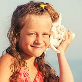 Girl on sea background. Child put the shell to her ear. Summer vacation stock image