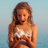 Girl on sea background. Child put the shell to her ear. Summer vacation royalty free stock images