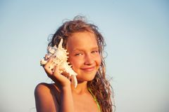 Girl on sea background. Child put the shell to her ear. Summer vacation stock images