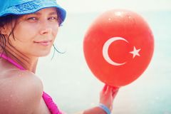 Girl on sea with balloon of Turkish flag in hand, Turkey. Tropical resort beach vacation stock photos