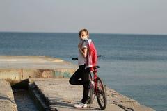 Girl, sea, bike Stock Photos