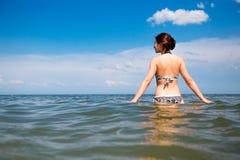Girl in the sea on blue sky stock photos