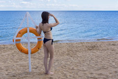 Girl on sea coast with lifebuoy Stock Photo