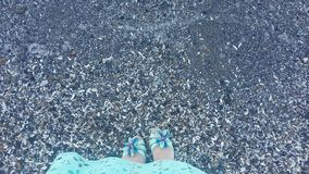 Girl by the sea, girl`s feet near the water Royalty Free Stock Photography