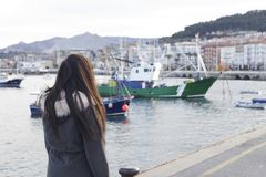 Girl on the sea harbor, looking at the boats. Brunette girl on the sea harbor, looking at the boats on the fishing port, in a little coastal town, at the Stock Images