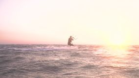 A girl on the sea kitesurfing at dawn, slow motion. Leaks. Beautiful woman in a suit for diving deals in kitesurfing at dawn stock video footage