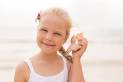 Girl by the sea listening to seashell Stock Images