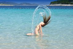 Girl in the sea with long hair. Young girl with long blonde hair in the sea Stock Image
