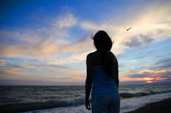 Girl and sea. Girl looks at the sea and enjoy the colors of the sunset Stock Photography