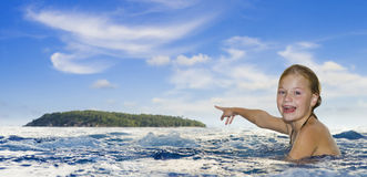 Girl in the sea pointing to an island Stock Images