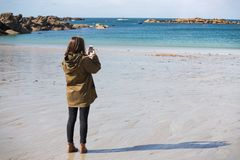 Girl and the Sea. Pretty girl walking on the shore of the sea at  the Tregastel and takes a photo on a smartphone, normandy. France stock photos