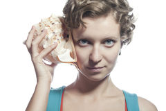 Girl with a sea shell to your ear. The beautiful curly-headed girl holds two cockleshells near ears and listens Stock Photography