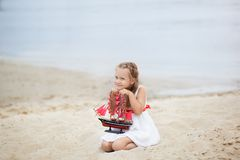 Girl on the sea with a ship. Close-up portrait of the girl`s face. little girl wait boat with scarlet sail. Girl on the beach in a stock image