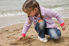 Girl on the sea. The girl on the shore of the sea, playing with sand Stock Images