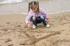 Girl on the sea. The girl on the shore of the sea, playing with sand Royalty Free Stock Image