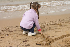 Girl on the sea. The girl on the shore of the sea, playing with sand Stock Photo