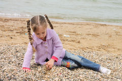 Girl on the sea. The girl on the shore of the sea, playing with sand Stock Image