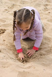 Girl on the sea. The girl on the shore of the sea, playing with sand Royalty Free Stock Photo