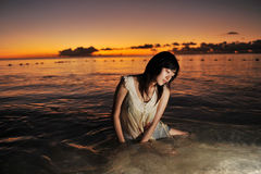 girl in the sea with the sunset  Stock Photos