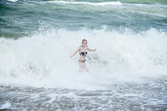 Girl in sea surf. Single happy young woman in swimsuit walking at sea surf with splashes royalty free stock photography