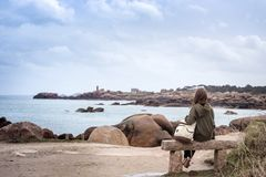 Girl and the Sea. Girl traveler sits on a bench near the sea and the shore at  the Tregastel, Brittany. France royalty free stock image