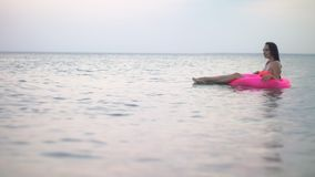 Girl in the sea on vacation. A girl in a pink bathing suit with a pink inflatable bath bathes in the blue sea in the evening stock video footage