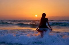 Girl at sea wave on sunset Royalty Free Stock Photography