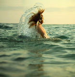 Girl in sea waves. The girl swiming in sea waves. An art photo. A beautiful landscape royalty free stock image